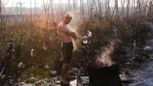 Bir mülteci soğuk havada yıkanmaya çalışıyor.