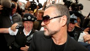 British singer George Michael is escorted out of Highbury Corner Magistrates Court in London, August 24, 2010