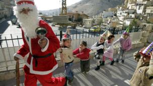 Noel baba kostümlü bir kişi, Şam'ın kuzeyindeki Hristiyan kasabası Maalula'da çocuklarla oynuyor