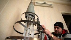 Akram Ebu el Foz boş roket fişeklerinden yaptığı Noel ağacını dekore ediyor