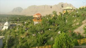 People sit on a hillside in Kandahar