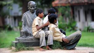 Boys sit by Gandhi statue