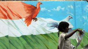 Indian child sells newspapers to commuters near a roadside mural in Bangalore