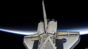 Space Shuttle Discovery is shown intersecting the thin line of Earth's atmosphere