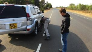 Ricky watches the car tyre being changed on the way to Dadaab