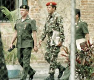 Venezuelan general Hugo Chavez walks escorted by military intelligence officers after being arrested for trying to overthrow Venezuela's government in a bloody coup February 5, 1992.
