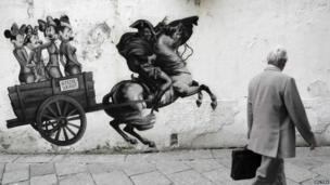 A man passes a cartoon on a wall in Milan mocking Silvio Berlusconi, 29 September 2011