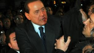 Silvio Berlusconi is rushed to safety after an attack in Milan, 13 December 2009