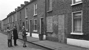 Three people examine terraced houses