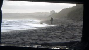 Man and dog walking on Aberdeen beach