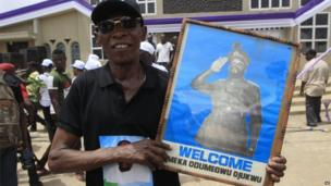 A man holds a picture of Chukwuemeka Ojukwu