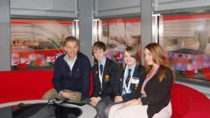 School Reporters from Tarporley High School pose with North West Tonight presenter, Roger Johnson, on the red sofa in MediaCity, Salford