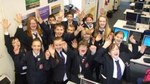 Student Reporters from Queen Elizabeth's Grammar School put their hands up and wave at the camera