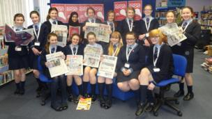 The girls from Archbishop Blanch School pose with newspapers in their hands in the library