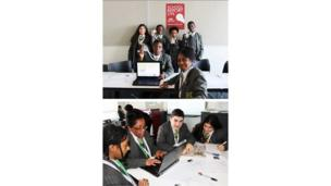 Skinners' Academy School Reporters sit at a desk and hold up their passes (Above). Students busy on their laptops (below).