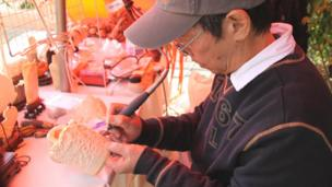 Man carving ornaments out of legal ivory
