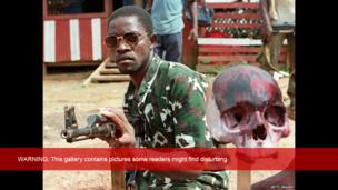 A rebel loyal to Charles Taylor holding Kalashnikov poses next to a painted skull of a Krahn ethnic soldier of president Samuel Doe, 15 May 1990 in Monrovia.