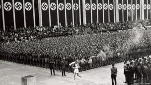 The torchbearer at the 1936 Olympic Games walks through a crowd.