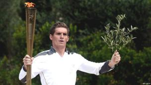 The first torch bearer, swimmer Spyros Gianniotis, runs with the Olympic flame on May 10, 2012 during the lighting ceremony at the ancient site of Olympia.