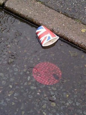 A paper cup in a puddle of rain