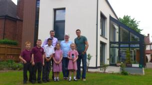 Joe in front of the 'eco home' with school kids, their teacher and the home's owner.