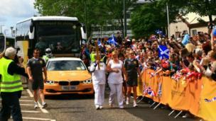 Crowds watch the Olympic torch as it passes