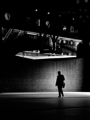 A man walking under offices at Broadgate, London