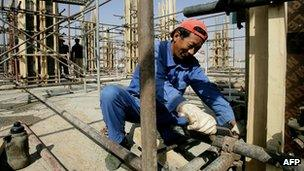 A Chinese worker fixes pipes at a construction site in Khartoum, Sudan