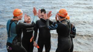 Swimmers 'high five' after a swim