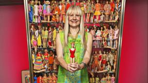 German woman posing with her award winning Barbie doll collection.
