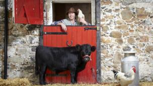 Farmer poses with the smallest bull in the world.