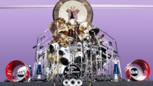 Owner of the world's largest drum set poses with his kit.
