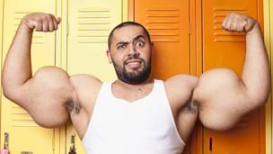 Man with largest biceps in the world poses for the camera.