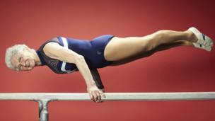 World's oldest gymnast balances on a bar.