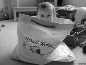 A toddler sitting in a paper bag
