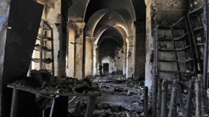 A Syrian rebel walks inside a burnt section of the Umayyad Mosque
