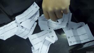 A hand drops their vote into the ballot box