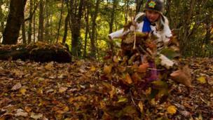 Natalie kicking leaves in a wood