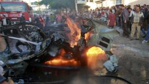 Crowds surround the burning wreckage of Ahmed Jabari's car.