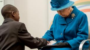 John, 12 presents the Queen a tablet computer with Jubilee Time Capsule entries on it