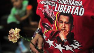 A woman who wears a shirt with the face of the President of Venezuela Hugo Chavez holds a flower during a mass held in La Merced Church, in Managua, to pray for the health of Hugo Chavez, on December 12, 2012