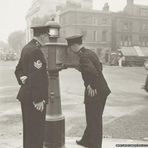 """Two officers with a """"police pillar"""" in September 1950"""
