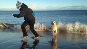 Jen and Sammy the retriever running along the beach