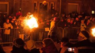 Crowds watch man swinging a fireball