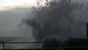 Waves break over the harbour wall