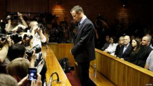 Photographers take pictures of Oscar Pistorius standing at the dock before the start of proceedings at a Pretoria magistrates court