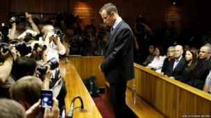 Oscar Pistorius stands at the dock