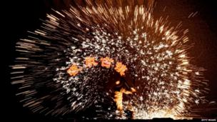 A blacksmith uses molten metal to create sparks during the Lantern Festival in Nuanquan in Heibei province.
