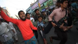 Activists carry a man injured in protests in Bogra, Bangladesh