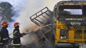 Fire-fighters try to douse flames of vehicle set alight by protesters, Rajshahi, Bangladesh
